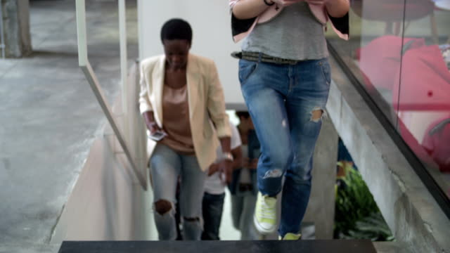 HD: Multi-ethnic young creative team walking up on the stairs. video