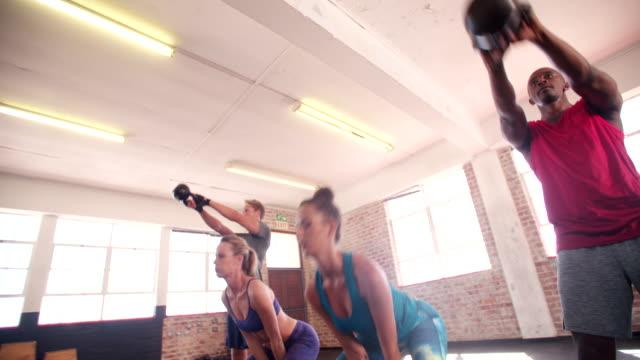 多民族の若者たちに焦点を当てたクロスフィット」でワークアウトジム - 有酸素運動点の映像素材/bロール