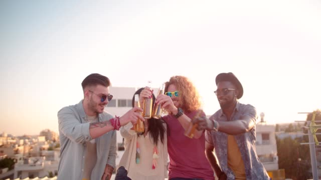 Multi-ethnic young friends toasting with beer at rooftop party video