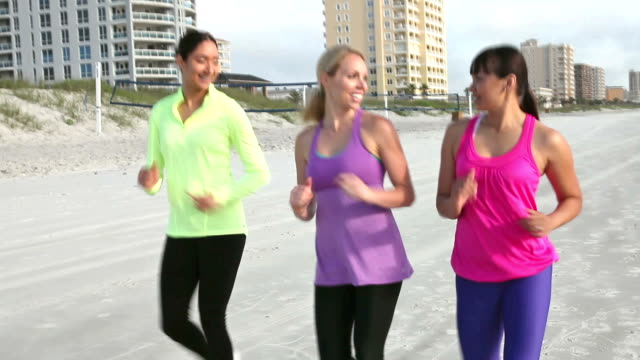 Multi-ethnic young women power walking on beach video