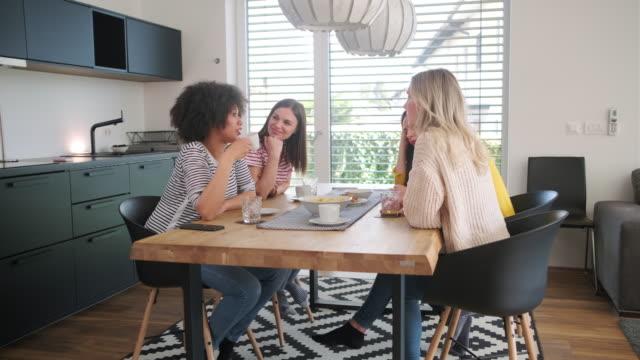 ダイニングテーブルで話す多民族の若い女性 - おやつ点の映像素材/bロール