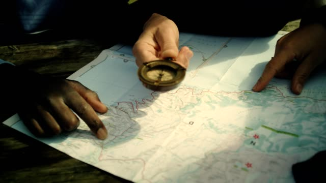 Multietnic group checking map Multietnic group planning trip. Using paper map. navigational compass stock videos & royalty-free footage
