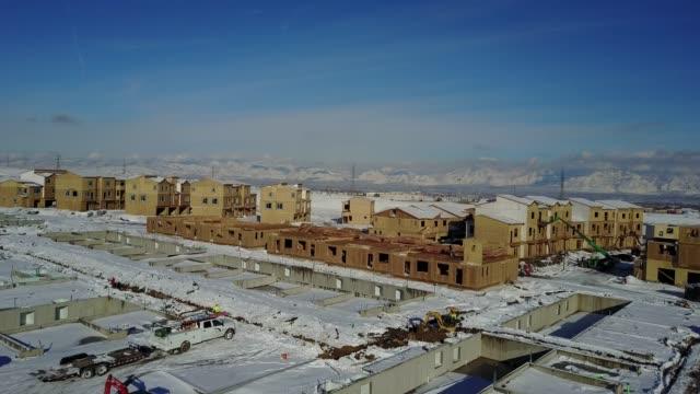 multi-family residential construction site under snow in winter - osiedle mieszkaniowe filmów i materiałów b-roll