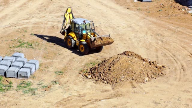 Multifunctional tractor-excavator Tractor digs the land, preparing the area for construction. Plot for the construction of the house. General view. construction vehicle stock videos & royalty-free footage