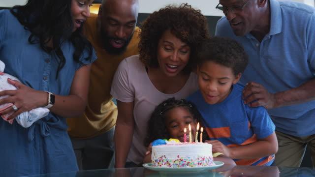 famiglia afroamericana multi-generazione che festeggia il compleanno delle nipoti a casa insieme - relazione umana video stock e b–roll