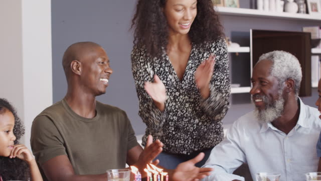 multi-generation family celebrating grandfathers birthday at home with cake and candles - nipote femmina video stock e b–roll