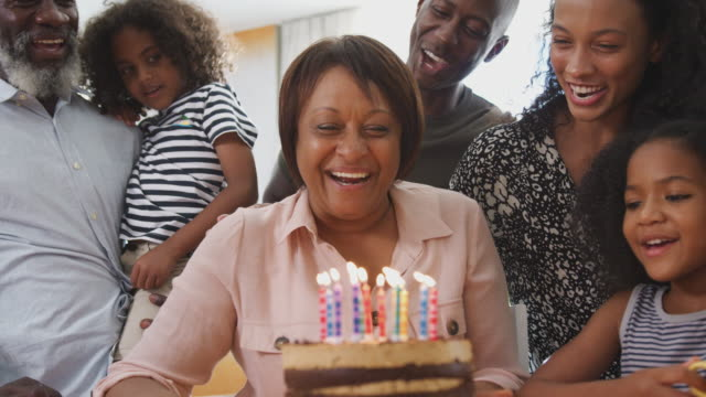 Multi-Generation Family Celebrating Grandmothers Birthday At Home With Cake And Candles Multi-generation family celebrating grandmothers birthday with cake as she blows out candles - shot in slow motion happy birthday stock videos & royalty-free footage
