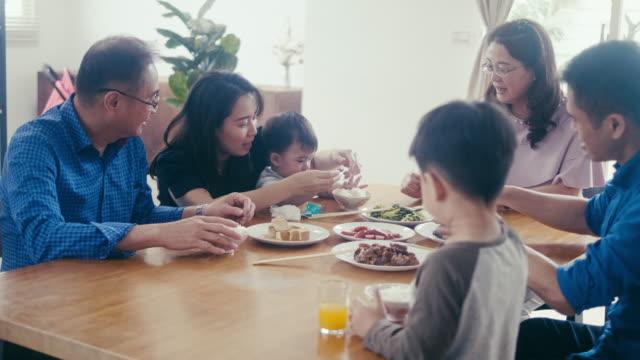 stockvideo's en b-roll-footage met familie van meerdere generaties genieten van het diner - breakfast table
