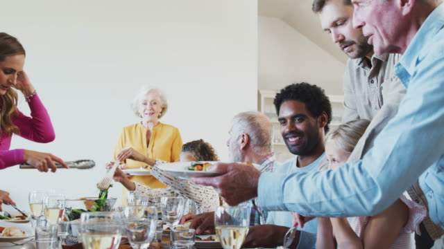 Multi-Generation Family Enjoying Meal Sitting Around Table At Home Together
