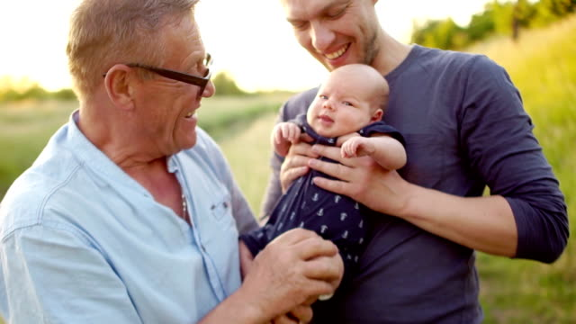 Multi-generation family. Grandfather kisses the foot of a newborn grandson. Three men rest on the nature, near the river. Colorful sunset video