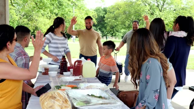 Multi-generation family greet one another during family reunion