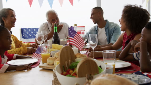 Multi-generation family having celebration meal Front view of an African American multi-generation family sitting at home around a dinner table decorated with US flags for an Independence Day celebration meal, talking and smiling, slow motion family 4th of july stock videos & royalty-free footage