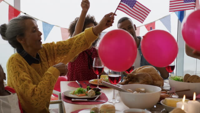 Multi-generation family having celebration meal Front view close up of an African American multi-generation family sitting at home around a dinner table decorated with US flags for an Independence Day celebration meal, waving flags and playing with balloons, slow motion family 4th of july stock videos & royalty-free footage
