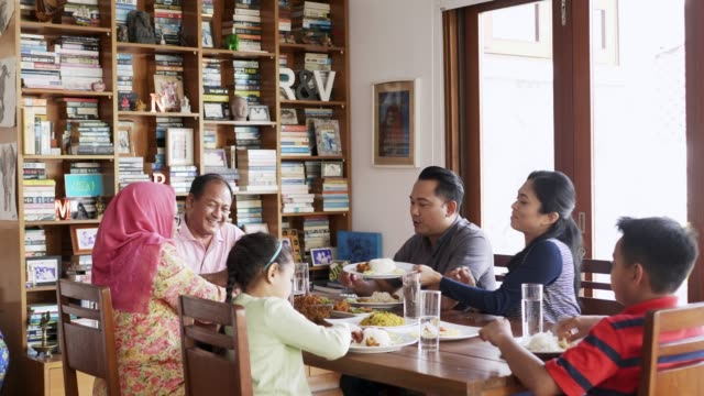 multi-generation family having food at table - etnia malese video stock e b–roll