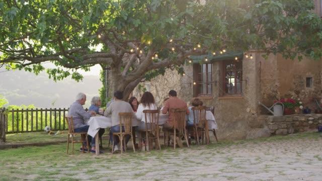 Multi-generation family having food outside house