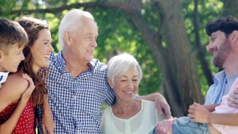 vídeos de stock e filmes b-roll de multi-generation family having fun in the park - family