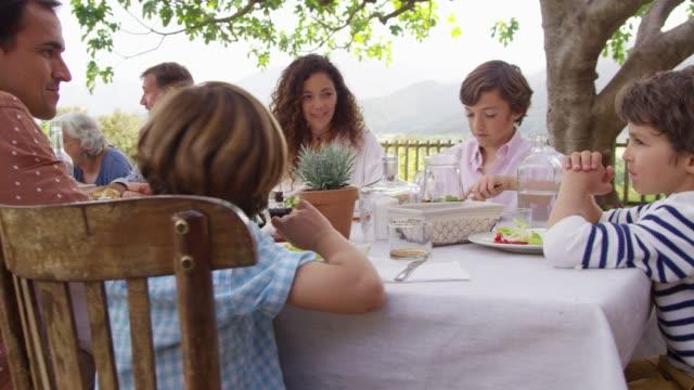 vídeos y material grabado en eventos de stock de familia de múltiples generaciones que almorzar fuera de casa - mesa muebles