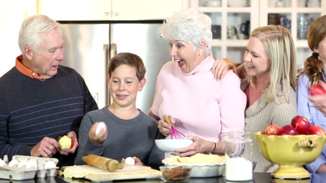 Multi-generation family in kitchen making an apple pie video