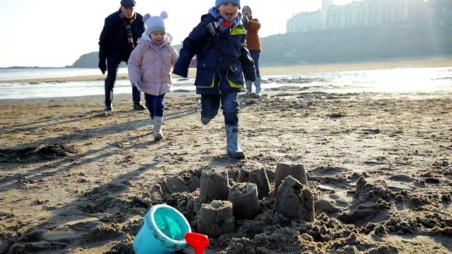 Várias gerações familiares pulando sobre castelos de areia! - vídeo