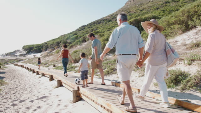 multi-generation family on summer vacation walking along wooden boardwalk on way to beach - несколько поколений семьи стоковые видео и кадры b-roll