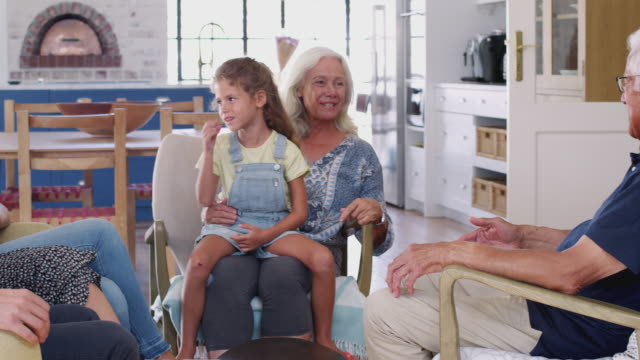 Multi-Generation Family Sitting On Sofas At Home Talking Together