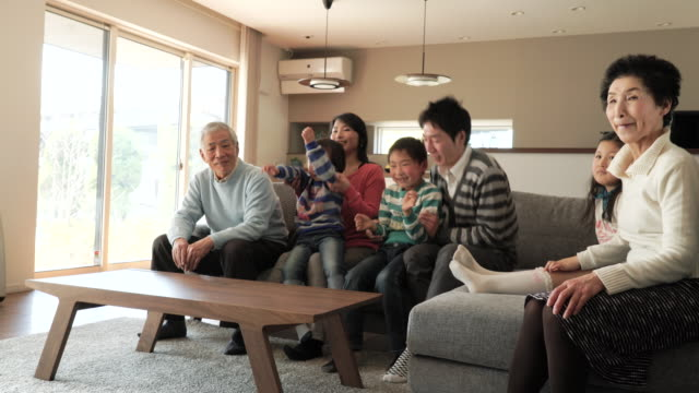 多世代家族でテレビをご覧のリビングルーム - 注視する点の映像素材/bロール