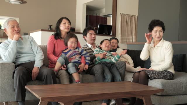 多世代家族でテレビをご覧のリビングルーム - 居間点の映像素材/bロール