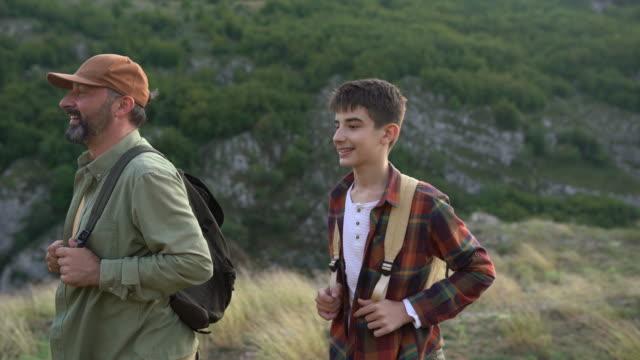 日没時に山で一緒にハイキングバックパックを持つ多世代の家族 - disruptagingcollection点の映像素材/bロール
