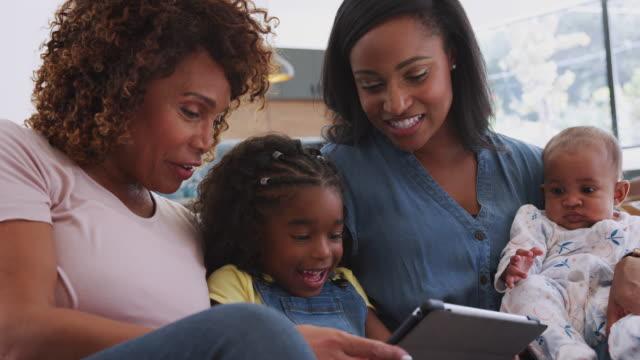 vídeos y material grabado en eventos de stock de familia afroamericana de varias generaciones sentada en el sofá en casa usando la tableta digital - usar la tableta digital