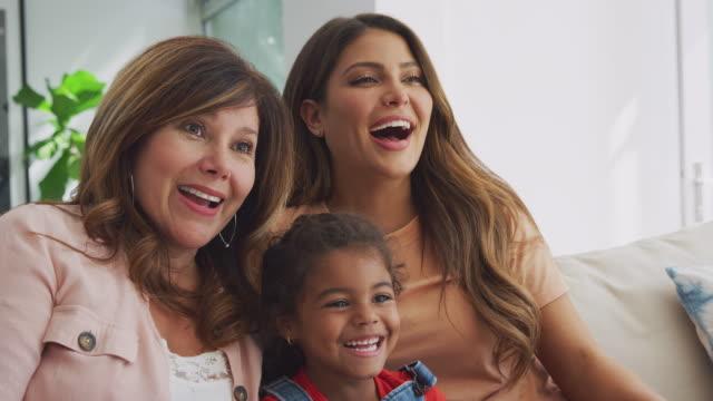 famiglia ispanica femminile multi-generazione sul divano a casa a guardare la tv insieme - relazione umana video stock e b–roll
