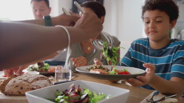 stockvideo's en b-roll-footage met multi-generatie gemengde race familie eten maaltijd rond tafel thuis samen - lunch
