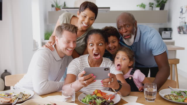 Video Multi-Generation Mixed Race Family Posing For Selfie As They Eat Meal Around Table At Home Together