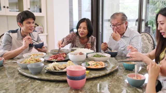 stockvideo's en b-roll-footage met multi-generation taiwanese familie verzameld voor de lunch thuis - oost azië