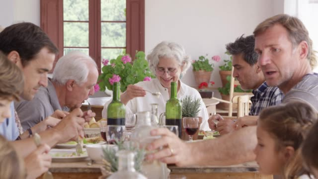 Multi-generational family enjoying food at home Dolly shot of parents having food with children. Multi-generational family is enjoying lunch together at home. They are sitting at dining table. medium group of people stock videos & royalty-free footage