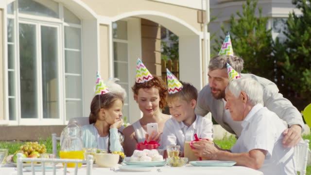 flergenerationsöverbryggande familj med selfie på outdoor födelsedags fest - birthday celebration looking at phone children bildbanksvideor och videomaterial från bakom kulisserna