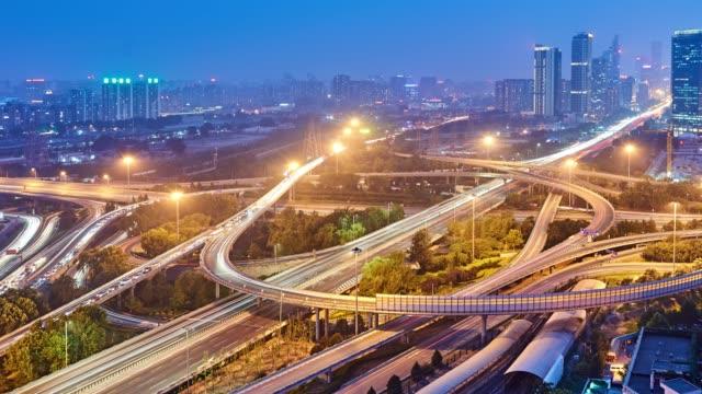 4k: viaduct med flera nivåer upptagen trafik vid solnedgången till natt tids fördröjning, peking, kina - blue yellow bildbanksvideor och videomaterial från bakom kulisserna