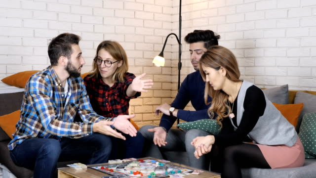 Multinational company sit on the couch and play monopoly board game, talk, discuss 50 fps video