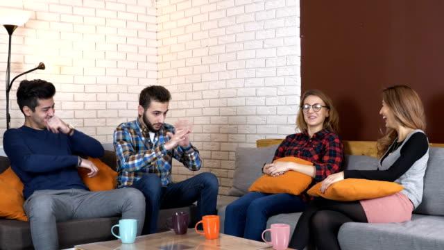 multinationale unternehmen auf der couch sitzen und reden, lachen 50 fps - storytelling videos stock-videos und b-roll-filmmaterial