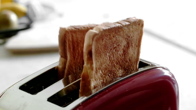 Multiple clips of toaster popping up toast video