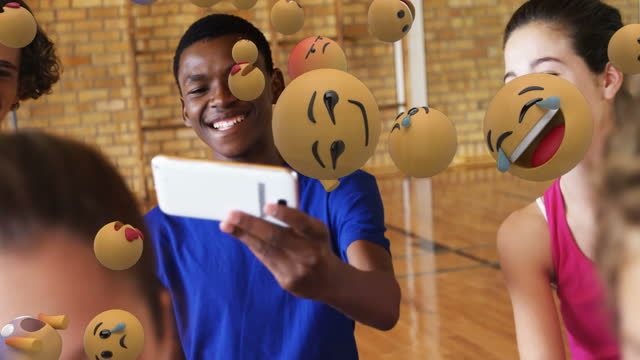 Multiple face emojis moving against students using smartphone