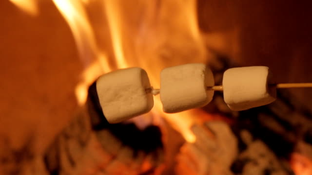 Multiple marshmallows extended over a fire to roast. video