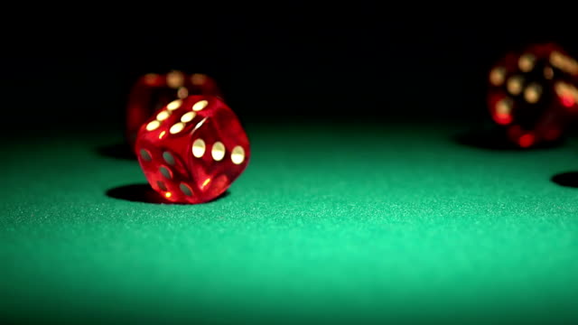 Multiple red dice rolling on green table. Beautiful casino background, video