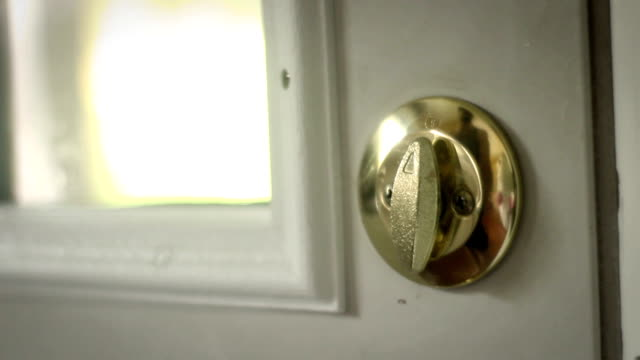 Multipurpose clip - Man locks and unlocks his double gold deadbolt lock on modern door video