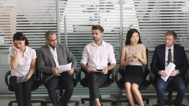 Multiracial applicants sitting in chair in queue wait job interview