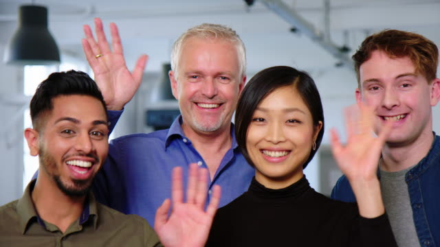 Multiracial business colleagues waving together and smiling