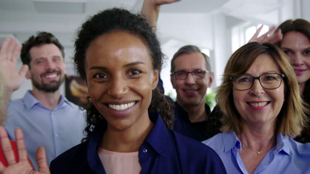 Multiracial business professionals waving hands in office Multiracial business group waving hands standing together in the office. Successful business professionals waving hands in office. human age stock videos & royalty-free footage
