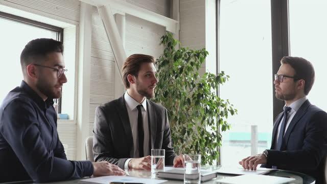 multiracial affärsmän i kostymer diskuterar avtal partnerskap detaljer vid mötet. - formell klädsel bildbanksvideor och videomaterial från bakom kulisserna