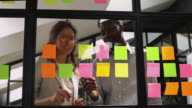 istock Multiracial colleagues managing project processes at kanban board. 1200420587