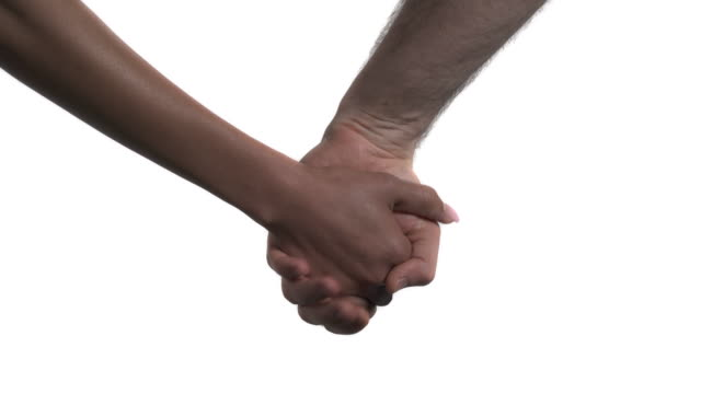 multiracial couple holding hands. love concept. isolated on white background - mano donna dita unite video stock e b–roll