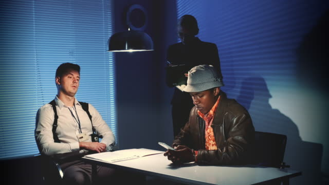 Multiracial desperate criminal writing last message on smartphone in interrogation room